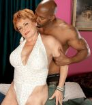 Crimson hair grannie X-rated film starlet Valerie blowing a humungous ebony dick in white lingerie