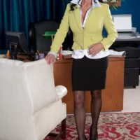 Stocking and mini-skirt garbed grandmother Rita Daniels stripping down to lingerie in work environment