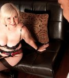 Busty mature XXX adult star Lola Lee providing oral pleasure in stockings and lingerie