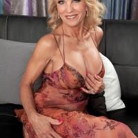Buxom blonde granny Cara Reid having big tits unleashed from bra by stud
