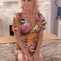 Over sixty blonde granny Cara Reid letting big knockers loose in bedroom