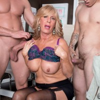 Hot blonde granny unleashes her big tits after tugging on a couple of dicks at once