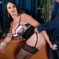 Mature businesswoman seduces an employee in her office wearing a black skirt