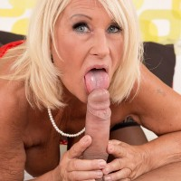 Gorgeous MILF over 60 licks and titty fucks her young lover's large cock on a bed