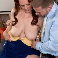 Aged redhead lady Katherine Merlot exposes large saggy tits in office