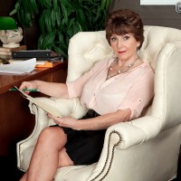60 + lady with short hair seduces a  younger gentleman during a session in her office