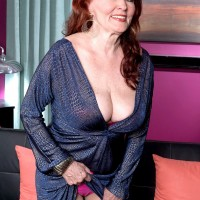 Mature redhead lets large tit fall free from dress while seducing younger man for sex
