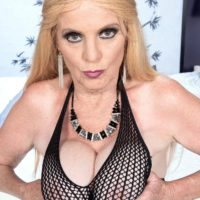 Blonde granny Charlie looses her enormous boobs in over the knee boots and a mesh body-stocking