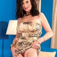 Older brown-haired X-rated film star Rita Daniels exposing massive hooters before bi-racial sex