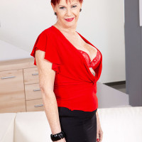 Over sixty redhead Caroline Hamsel plays with her boobs while wearing crotchless panties