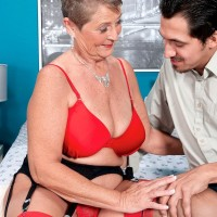 Short haired granny Joanne Price seducing younger stud in stockings and garter