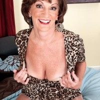 Solo granny Sydni Lane taunting on bed by showcasing melon-holder in nylons