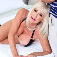 Sumptuous grandma Leah L'Amour deep throats a giant cock while her hubby sleeps