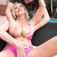 Tempting 60 plus lady Katia has her giant boobs massaged by a junior man on the patio