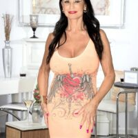 Top granny X-rated film starlet Rita Daniels uncovers her massive titties and flashes her underwear too